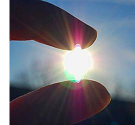 image of finger and thumb positioned as if holding the sun